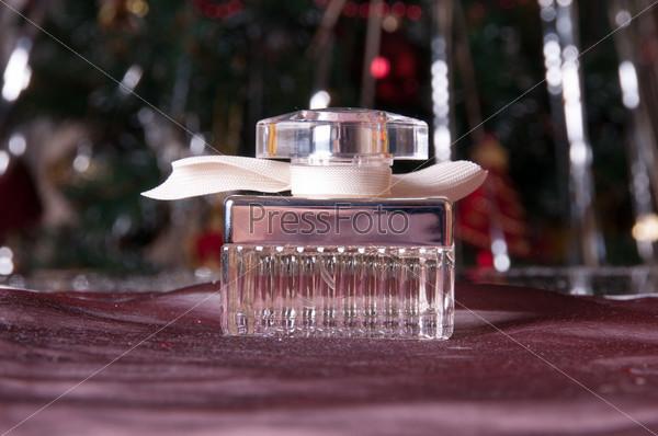 Фотография на тему Флакон на столе и новогодняя елка