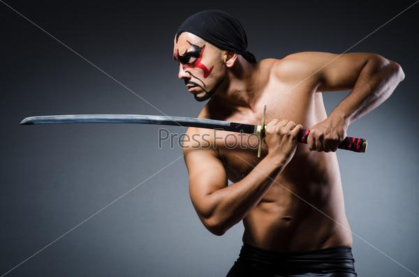 Мужчина с мечом и раскрашенным лицом