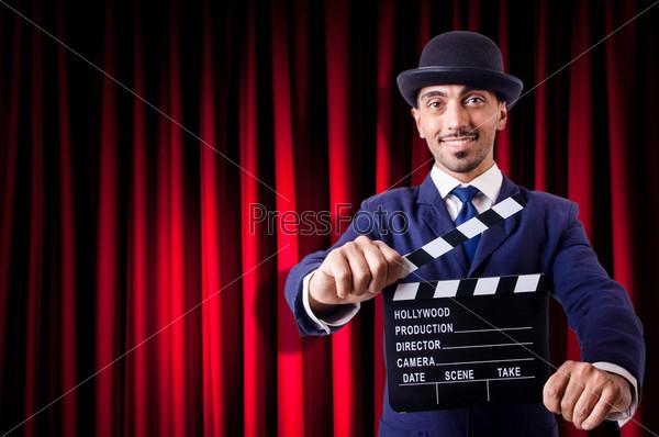 Мужчина с кино-хлопушкой на фоне занавеса