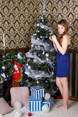 Фотография на тему Девушка наряжает Рождественскую елку