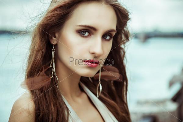 Прекрасная девушка с длинными темными волосами на фоне реки
