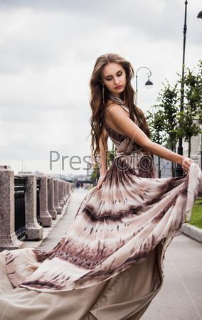 Фотография на тему Прекрасная девушка в длинном развевающемся платье на фоне набережной