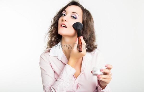 Молодая женщина наносит пудру для лица с помощью кисти