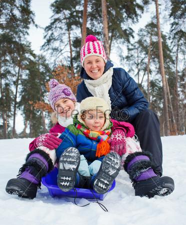 Семья катается на санках на фоне зимнего пейзажа