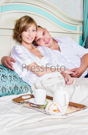 Молодая красивая семья завтракает в светлых апартаментах
