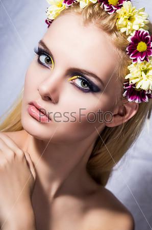 Портрет юной девушки с идеальной кожей, ярким макияжем и цветами в волосах