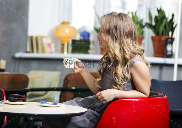 Фотография на тему Женщина держит чашку кофе и улыбается