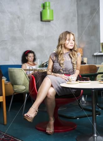Женщина сидит на стуле, глядя в сторону