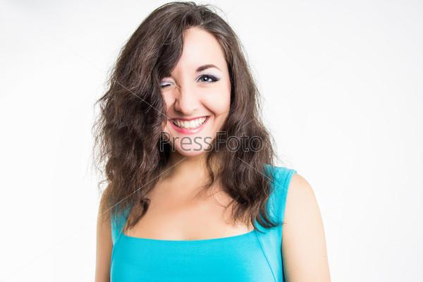 Портрет эмоциональной подмигивающей девушки на белом фоне