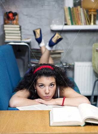 Задумчивая молодая женщина лежит на диване