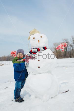Фотография на тему Мальчик делает снеговика