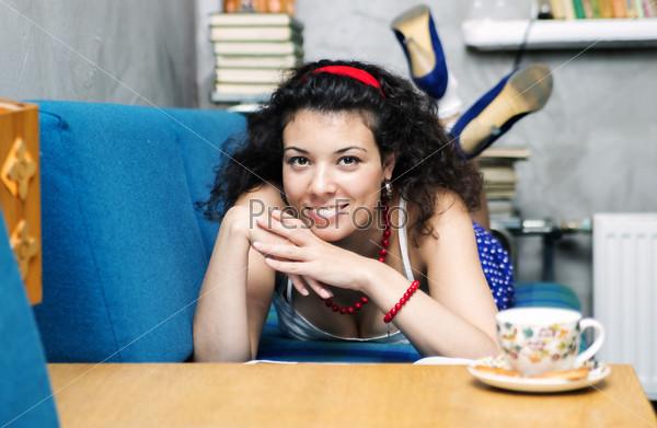 Фотография на тему Женщина лежит на диване и широко улыбается