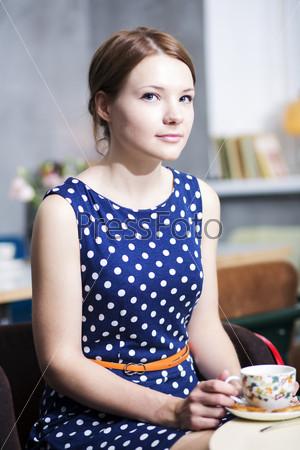 Фотография на тему Женщина в платье в белый горошек в кафе