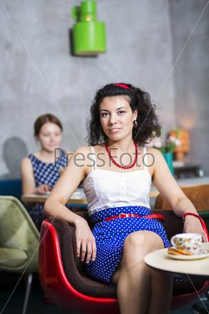 Улыбающаяся женщина на стуле в кафе
