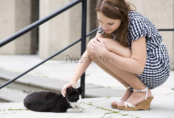 Женщина в клетчатом платье гладит уличную кошку