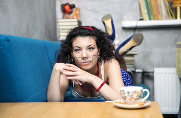 Фотография на тему Женщина лежит на мягком диване и смотрит