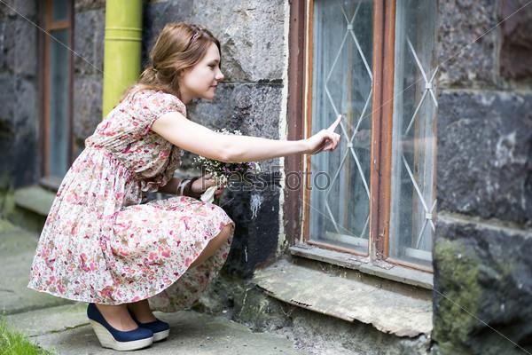 Фотография на тему Женщина в платье рисует на оконном стекле