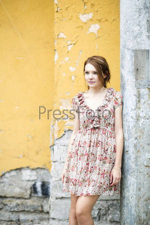 Женщина в платье с цветочным принтом думает о чем-то