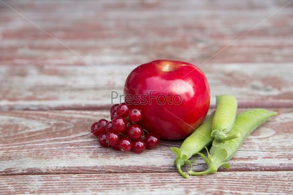 Спелые брусника, красное яблоко и стручки гороха
