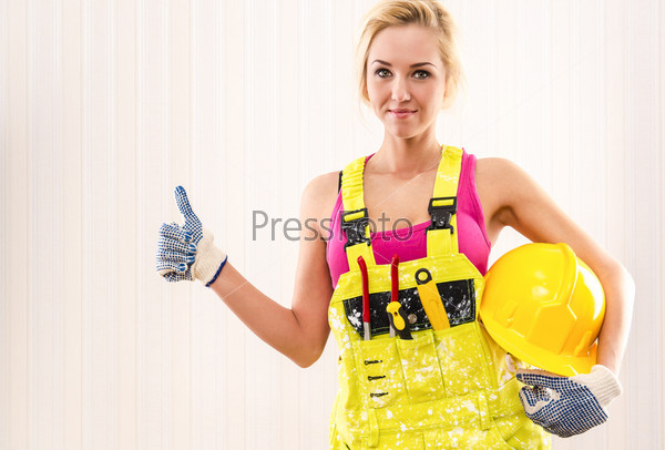 Фотография на тему Женщина в комбинезоне держит каску и показывает палец вверх