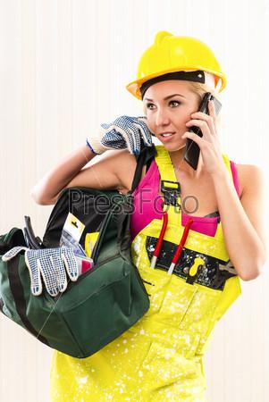 Женщина-строитель держит инструмент и разговаривает по телефону