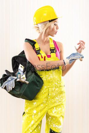 Фотография на тему Женщина-строитель держит сумку с рабочим инструментом в помещении