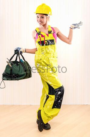 Женщина-строитель держит сумку с рабочим инструментом в помещении