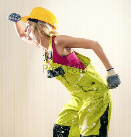 Фотография на тему Женщина в комбинезоне и каске позирует в помещении