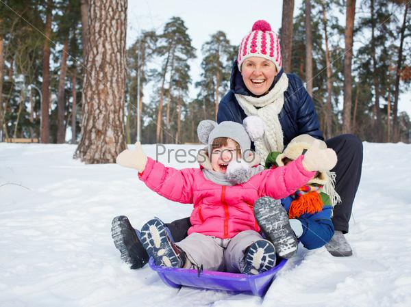Фотография на тему Семья катается на санках зимой