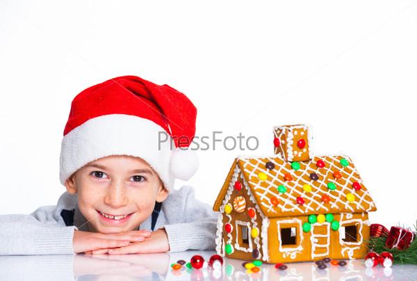 Фотография на тему Мальчик в шапке Санта-Клауса с пряничным домом