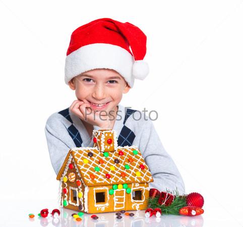 Мальчик в шапке Санта-Клауса с пряничным домом