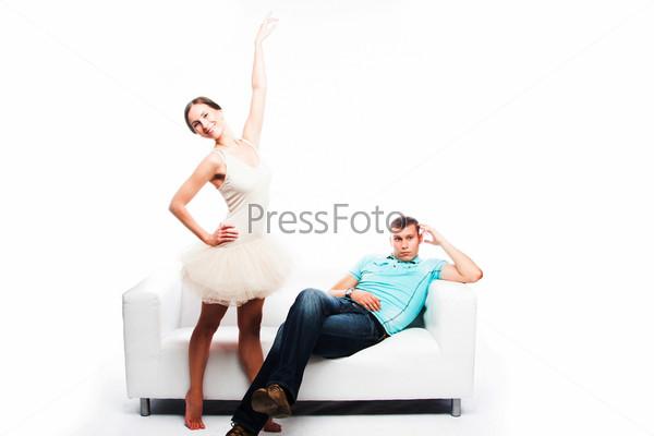 Молодая и красивая балерина искушает своим танцем мужчину, сидящего на белом диване