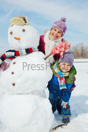 Фотография на тему Дети делают снеговика