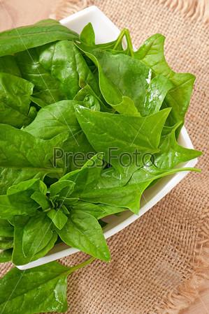 Промытые листья шпината в миске на деревянном столе