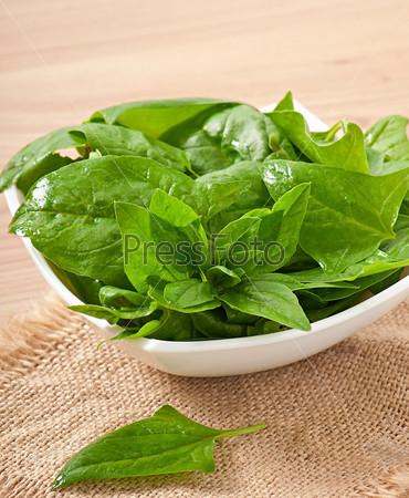 Фотография на тему Промытые листья шпината в миске на деревянном столе