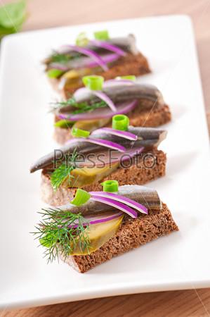 Бутерброды из ржаного хлеба с сельдью, луком и зеленью