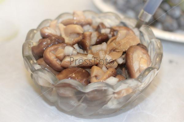 Фотография на тему Маринованные грибы в хрустальной вазе как часть праздничного ужина