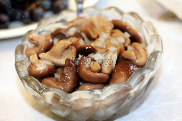 Маринованные грибы в хрустальной вазе как часть праздничного ужина