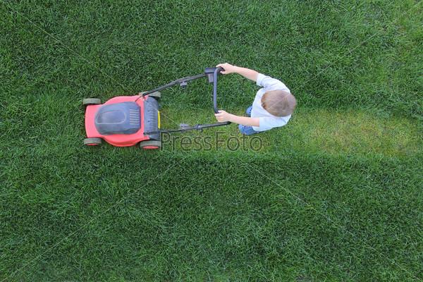 Фотография на тему Маленький мальчик подстригает траву газонокосилкой