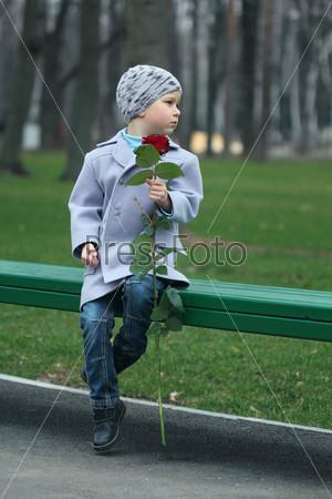 Маленький мальчик ждет в парке