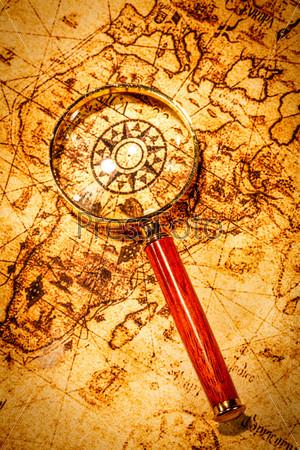 Фотография на тему Старинное увеличительное стекло лежит на карте античного мира