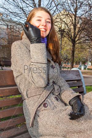 Красивая и молодая женщина отдыхает в парке осенью