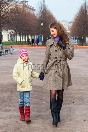 Фотография на тему Молодая мать гуляет с красивой дочерью в парке