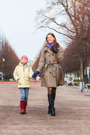 Молодая мать гуляет с красивой дочерью в парке