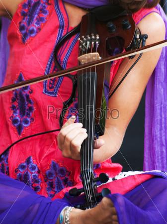 Фотография на тему Руки музыканта, играющего на электрической скрипке