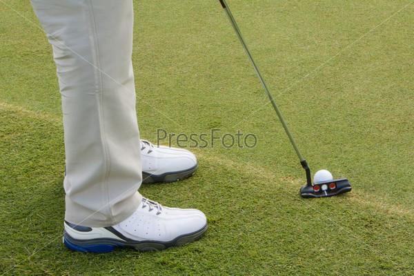 Фотография на тему Ноги, клюшка и мяч для гольфа на траве