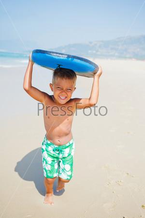 Веселый мальчик с доской для серфинга