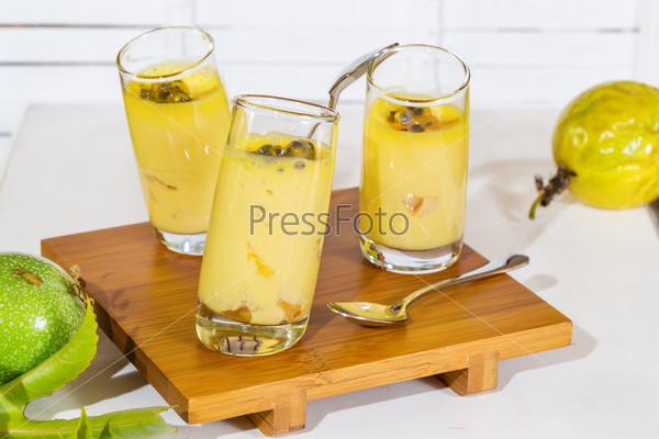Фотография на тему Три симметричных бокала с фруктовым десертом на деревянном поддоне