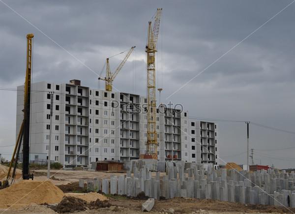 Фотография на тему Строительство нового дома на фоне вбитых свай