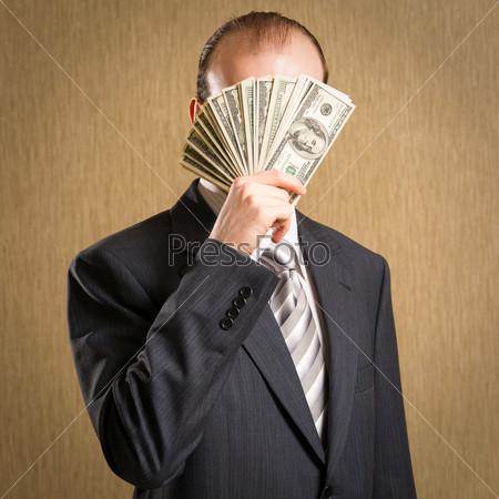 Человек скрывает лицо пачкой денег